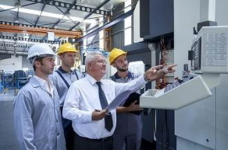 Man showing control panel to workers